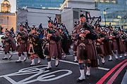 A Scottish regiment is led past Victoria by its Pipe Band on its way to Westminster Abbey - Remembrance Sunday and Armistice Day commemorations fall on the same day, remembering the fallen of all conflicts but particularly the centenary of the end of World War One.
