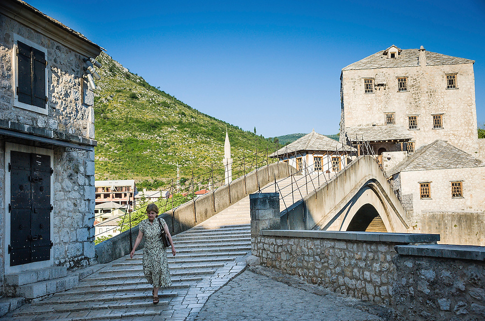 MOSTAR, BOSNIA AND HERZEGOVINA - JUNE 26:  A woman walk along the Old Bridge on  June 26, 2013 in Mostar, Bosnia and Herzegovina.The Siege of Mostar reached its peak and more cruent time during 1993. Initially, it involved the Croatian Defence Council (HVO) and the 4th Corps of the ARBiH fighting against the Yugoslav People's Army (JNA) later Croats and Muslim Bosnian began to fight amongst each other, it ended with Bosnia and Herzegovina declaring independence from Yugoslavia.  (Photo by Marco Secchi/Getty Images)