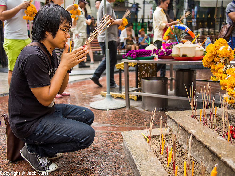 19 JULY 2013 - BANGKOK, THAILAND:   A man prays at Erawan Shrine in Bangkok. The Erawan Shrine (Thai: San Phra Phrom) is a Hindu shrine in Bangkok, Thailand, that houses a statue of Phra Phrom, the Thai representation of the Hindu creation god Brahma. A popular tourist attraction, it often features performances by resident Thai dance troupes, who are hired by worshippers in return for seeing their prayers at the shrine answered.    PHOTO BY JACK KURTZ