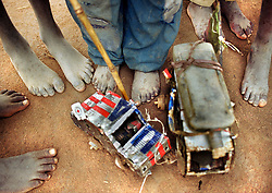 Displaced Angolan children create toys out of cans that brought food distributed by the United States government in a refugee camp in Huambo in March, 2000. Angola's brutal 26 year-civil war has displaced around two million people - about a sixth of the population - and 200 die each day according to United Nations estimates. .(Photo by Ami Vitale).