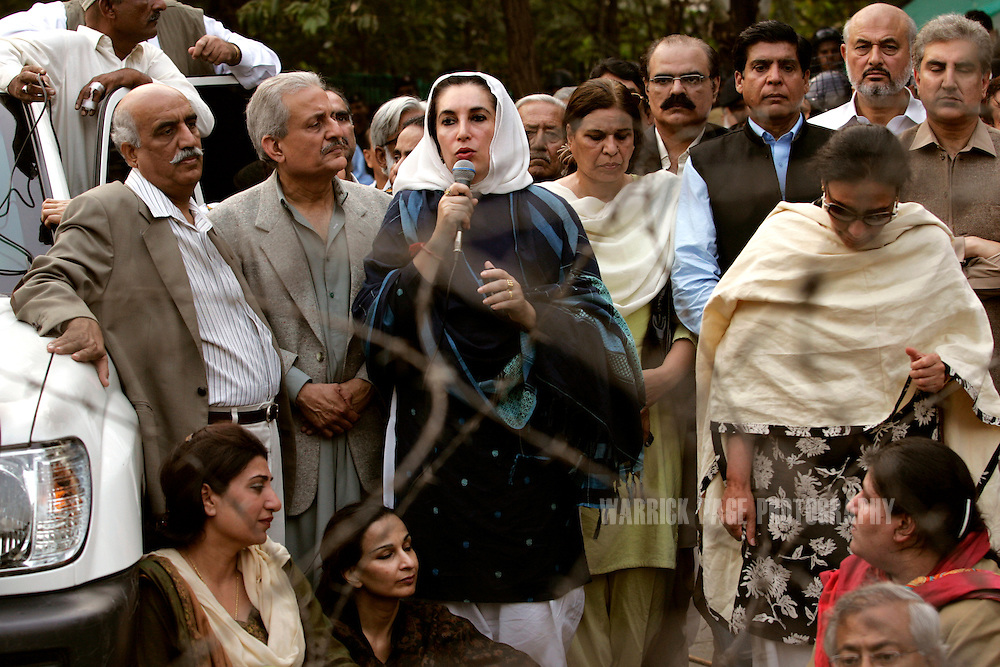 ISLAMABAD, PAKISTAN - NOVEMBER 09:  Former Pakistani Prime Minister, Benazir Bhutto speaks to media from behind barbed-wire after breaking through police lines outside her home on November 9, 2007 in Islamabad, Pakistan. Bhutto was placed under house arrest to prevent her from participating in a planned rally by her political party, the Pakistan People's Party (PPP). Bhutto broke through police lines outside her home to address the media and condemn the move by President Musharraf  and urge him to stick to his commitments of removing his uniform and holding elections. The president declared emergency rule on Saturday, just days before the Supreme Court was to decide on the legitimacy of Musharraf's presidency. (Photo by Warrick Page)