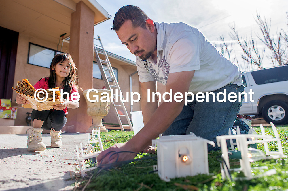 110113       Cable Hoover<br /> <br /> Aylin Andablo, left, helps family friend Manuel Benitez install electric holiday luminarias at her home in Gallup Friday.