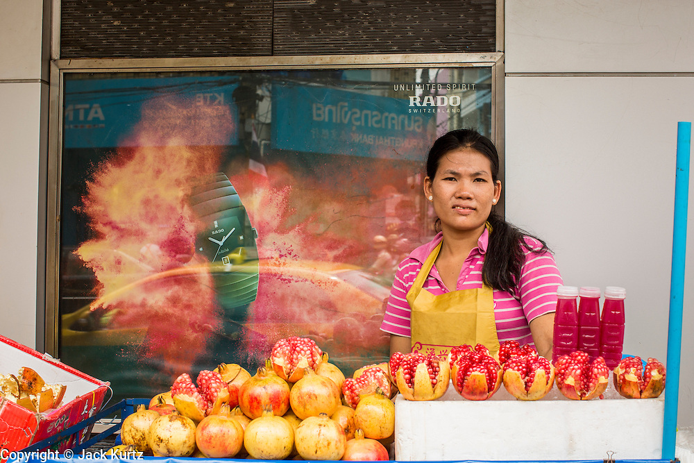 14 OCTOBER 2012 - BANGKOK, THAILAND:  A pomegranate juice vendor in Bangkok's Chinatown with Vegetarian Festival flags behind him. The Vegetarian Festival is celebrated throughout Thailand. It is the Thai version of the The Nine Emperor Gods Festival, a nine-day Taoist celebration beginning on the eve of 9th lunar month of the Chinese calendar. During a period of nine days, those who are participating in the festival dress all in white and abstain from eating meat, poultry, seafood, and dairy products. Vendors and proprietors of restaurants indicate that vegetarian food is for sale by putting a yellow flag out with Thai characters for meatless written on it in red.    PHOTO BY JACK KURTZ