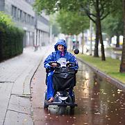 Foto: David Rozing Nederland Rotterdam 27 juli 2013 20130727 Noodweer in Nederland, zware onweersbuien teisteren Rotterdam. In korte tijd valt er een enorme hoeveelheid regenwater.Oudere dame in scootmobiel trotseert het weer.  Foto: David Rozing
