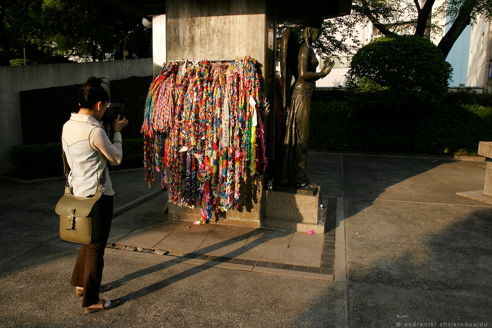 Hiroshima Peace Memorial Park. Japanese visitor photographing the paper cranes, left as peace offerings on the Memorial tower monument to the mobilized students who died in the bombing.
