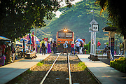 "07 JANUARY 2013 - KANCHANABURI, THAILAND: A vendor runs across the tracks while a Thai passenger train crosses ""Bridge On the River Kwai"" in Kanchanaburi, Thailand. Hundreds of thousands of Asian slave laborers and Allied prisoners of war died in World War II making the railway between Bangkok and Rangoon (now Yangon), Burma (now Myanmar) for the Japanese.  Thailand has a very advanced rail system and trains reach all parts of the country.    PHOTO BY JACK KURTZ"