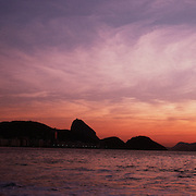 Sunrise at Rio de Janeiro's Copacabana beach, Copacabana with Sugar Loaf mountain in the distance. Rio de Janeiro, Brazil. 11th December 2011. Photo Tim Clayton..
