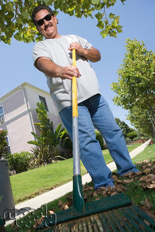 Portrait of man raking lawn in garden