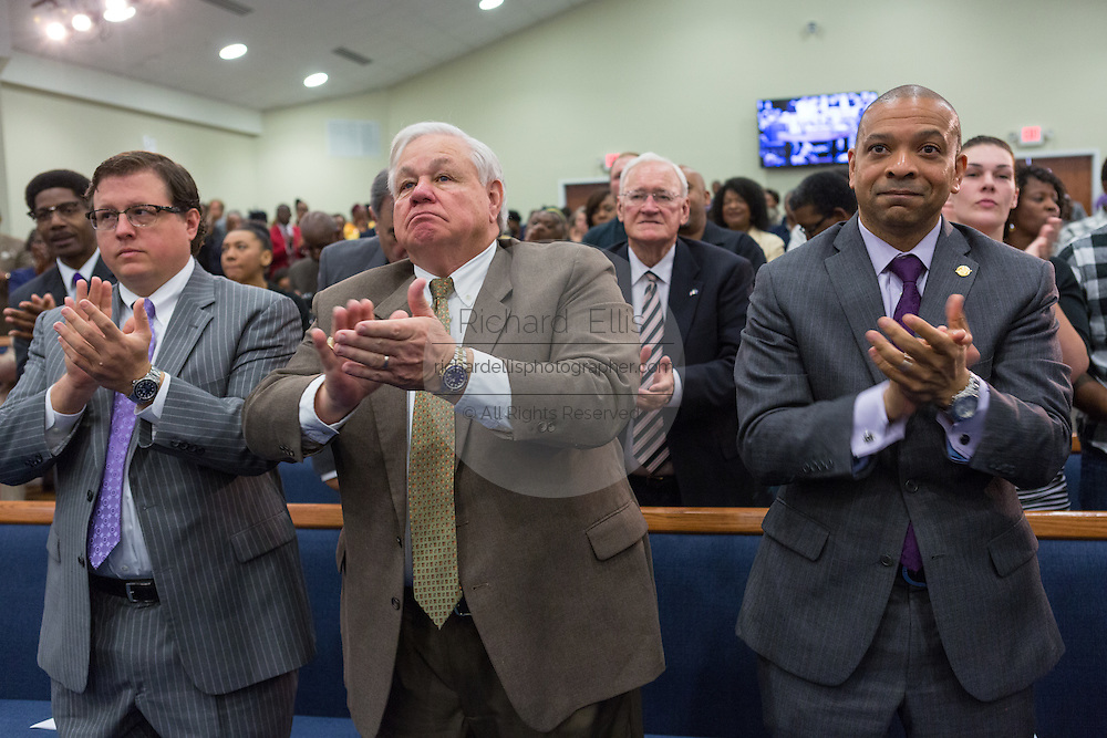 North Charleston Mayor Keith Summey (center) applauds Rev. Al Sharpton during a healing service at Charity Missionary Baptist Church April 12, 2015 in North Charleston, South Carolina. Sharpton spoke following the recent fatal shooting of unarmed motorist Walter Scott police and thanked the Mayor and Police Chief for doing the right thing in charging the officer with murder.