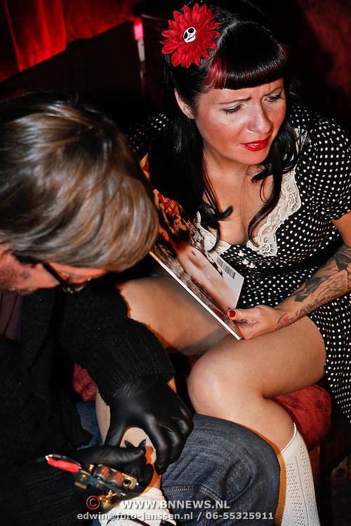 NLD/Amsterdam/20101008 - Onthulling Playboy cover Sanne Kraaijkamp, logo getatoeerd op haar been door hoofdredacteur Jan Heemskerk