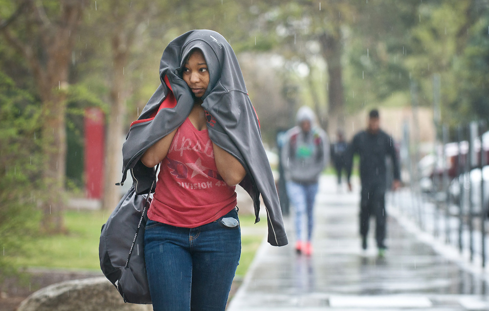 mkb032817b/metro/Marla Brose --  Damani Tryon, a University of New Mexico psychology student, cover herself with a jacket while heading home after classes, Tuesday afternoon, March 28, 2017 in Albuquerque, N.M. (Marla Brose/Albuquerque Journal)