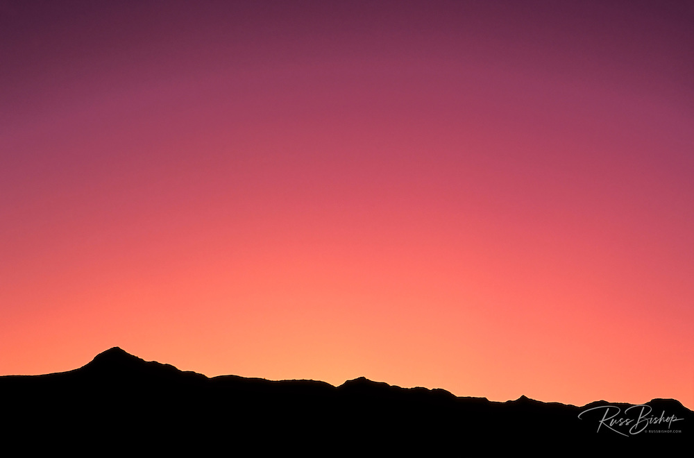 Pink dawn light over silhouette of the Badlands, Badlands National Park, South Dakota