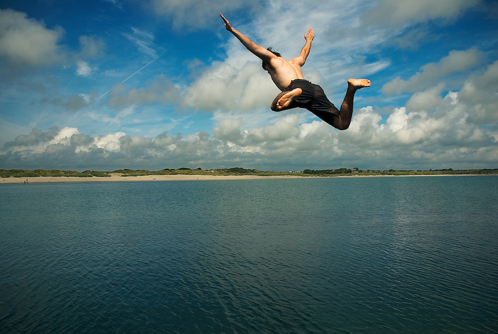 A swimmer frozen mid air as he leaps off the pier at Carne Beach, Co. Wexford, Ireland.