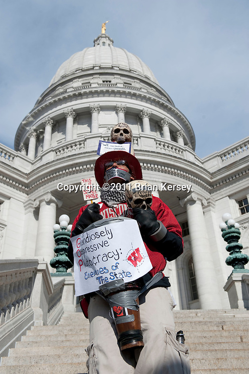 "A silent protester walks the grounds of the state Capital on March 1, 2011 in Madison, Wisconsin. Despite a court order issued Tuesday mandating that the state Capitol should be opened to the public ""during business hours and at times when governmental matters, such as hearings, listening sessions and court arguments are being conducted"" the Capitol remained closed to the public.      (Photo by Brian Kersey)"