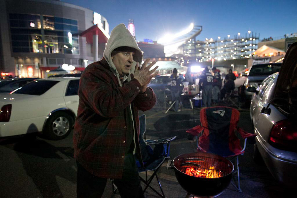 Foxborough, MA 01/14/2012.Jim Kadlick of Quincy warms his hands over the barbecue grill while tailgating outside Gillette Stadium before the start of Saturday's AFC Divisional game between the Patriots and the Denver Broncos..Wicked Local Photo by Alex Jones