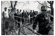 March, 2002.Pec/Peja, Kosovo.Men gather to watch an exhumation near Pec/Peje, while an Italian soldier guards the entrance to the site. The United Nations police do not allow spectators, including relatives or neighbors.