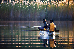 Two local village boys fishing in the Delta from a traditional mokoro, Okavango Delta, Botswana,Africa