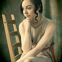 Young woman seated on chair and deep in thought