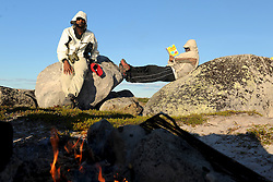 """Sanjayan Muttulingam, left and Tristen Jade Lockhart, 14 relax at a campsite in the Thelon, the largest and most remote game sanctuary in North America, which almost no one has heard of.  For the Akaitcho Dene, the Upper Thelon River is """"the place where God began.""""  Sparsely populated, today few make it into the Thelon. Distances are simply too far, modern vehicles too expensive and unreliable. For the Dene youth, faced with the pressures of a western world, the ties that bind the people and their way of life to the land are even more tenuous. Every impending mine, road, and dam construction threatens to sever these connections. In July and August, 2011 a group of youth paddled to their ancestral hunting ground and spiritual abode.  this next generation of young leaders will be the ones who will need to speak for the Thelon the loudest. (Photo by Ami Vitale)"""