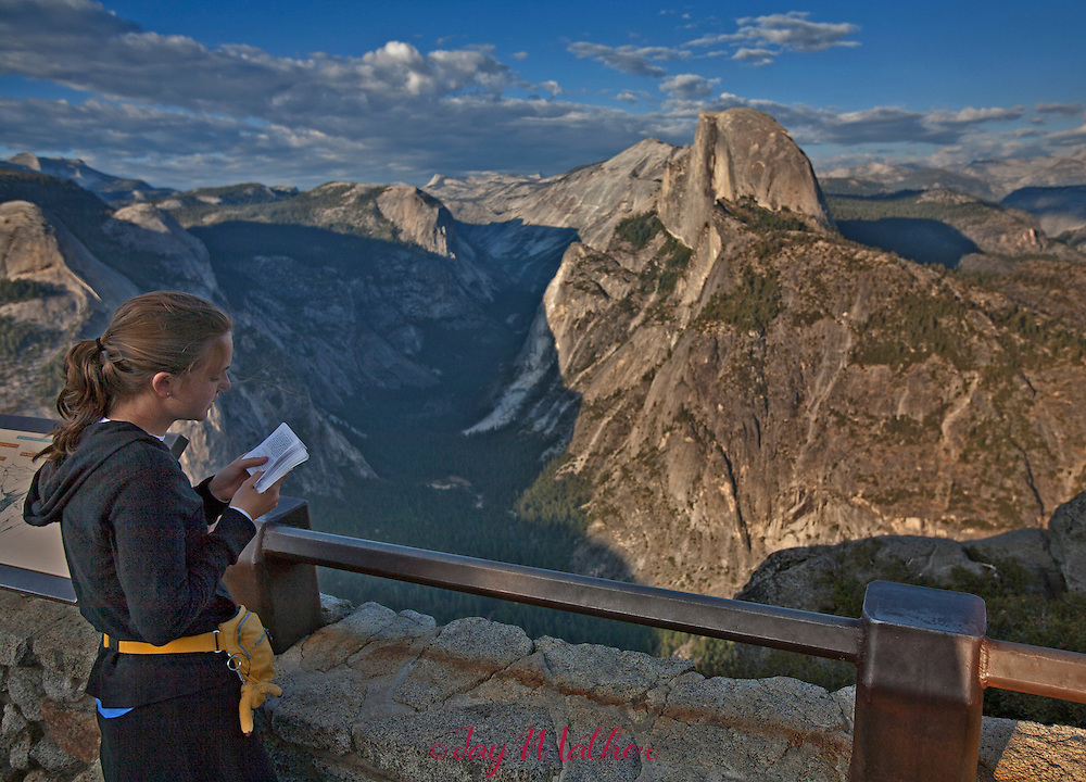 A young Jewish women visiting Glacier Point at sunset reads a prayer from her book.