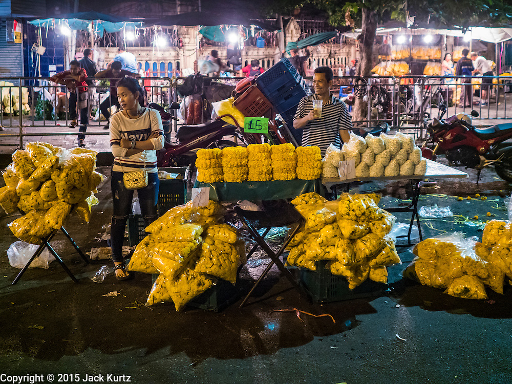 "21 DECEMBER 2015 - BANGKOK, THAILAND: Marigold vendors on the street in Pak Khlong Talat, also called the Flower Market. The market has been a Bangkok landmark for more than 50 years and is the largest wholesale flower market in Bangkok. A recent renovation resulted in many stalls being closed to make room for chain restaurants to attract tourists. Now Bangkok city officials are threatening to evict sidewalk vendors who line the outside of the market. Evicting the sidewalk vendors is a part of a citywide effort to ""clean up"" Bangkok.       PHOTO BY JACK KURTZ"