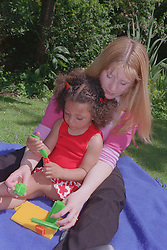 Teenage mother sitting on picnic blanket in garden behind young daughter playing with stickle bricks,