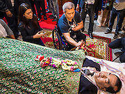 27 JANUARY 2014 - BANGKOK, THAILAND:  A man in a wheelchair participates in the bathing rites for anti-government leader Suthin Taratin at Wat Sommanat Rajavaravihara in Bangkok. In Thai tradition, after death a bathing ceremony takes place in which relatives and friends pour water over one hand of the deceased. Suthin was a core leader of the People's Democratic Force to Overthrow Thaksinism (Pefot), one of several organizations leading protests against the elected government of Thai Prime Minister Yingluck Shinawatra. He was murdered Sunday, Jan. 28, while he was leading a rally to prevent voters from reaching a polling center in the Bang Na district of Bangkok.    PHOTO BY JACK KURTZ