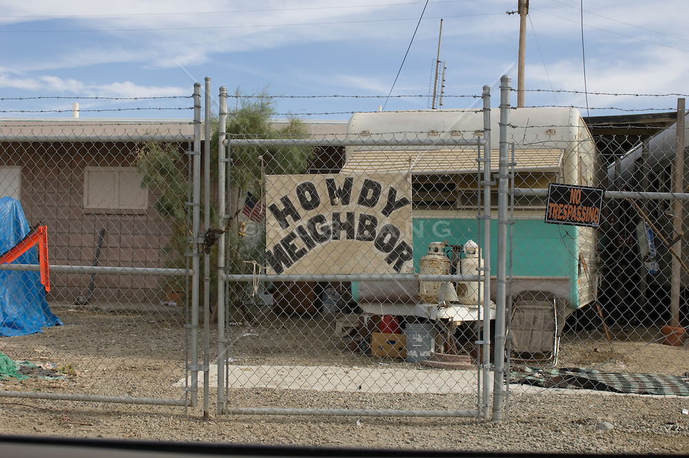chained link fence with friendly sign in a trailer park