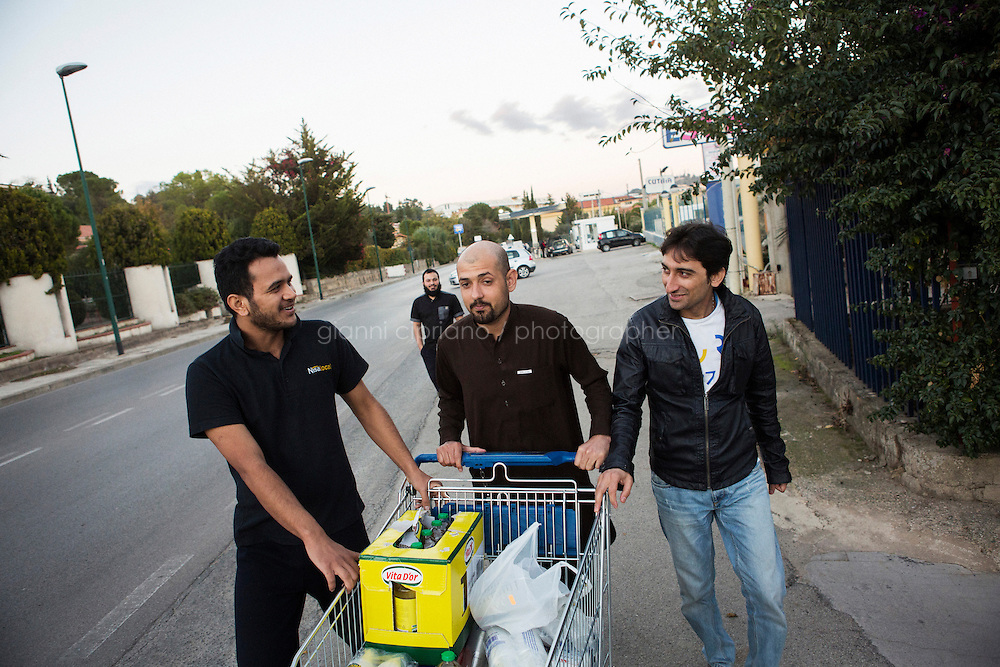 CALTANISSETTA, ITALY - 13 NOVEMBER 2014: Pakistani asylum seekers walk back to the Pian del Lago CARA (Accommodation Centre for Asylum Seekers) with a cart of purchased juices and sodas in Caltanissetta, Italy, on November 13th 2014. To this date, the Pian de Lago CARA hosts 491 asylum seekers, while 40 illegal immigrants are held in the CIE (Center for Identification and Deportation), before being deported.
