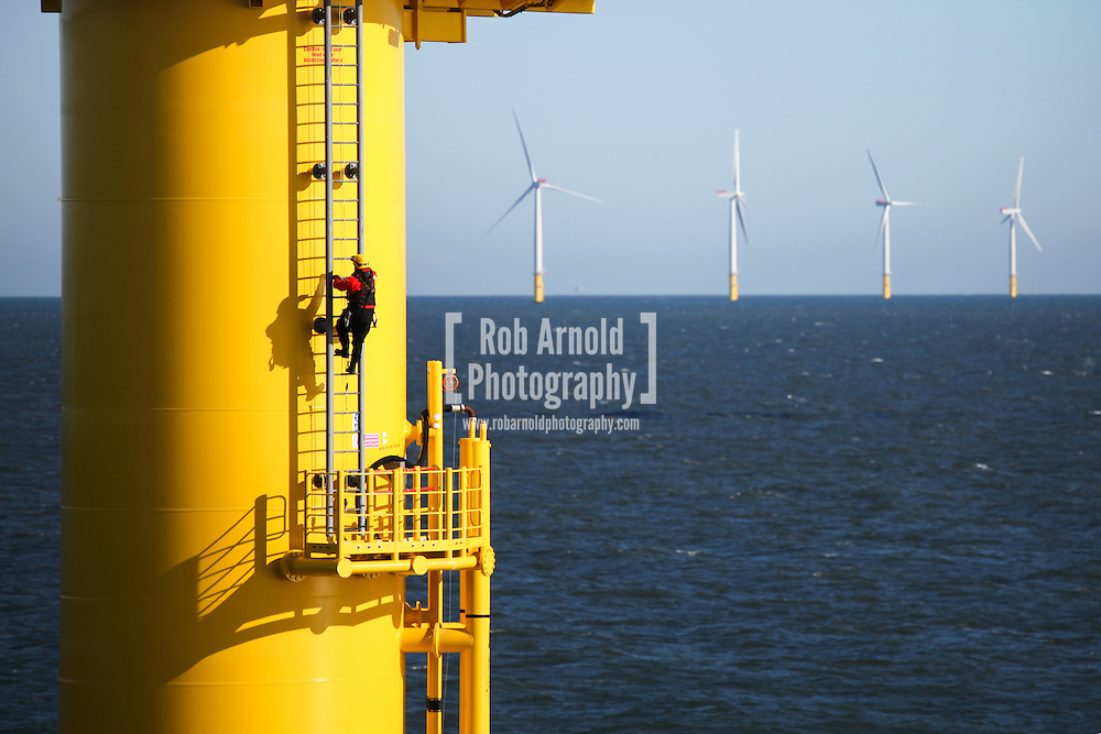 © Rob Arnold.  24/03/2014. North Wales, UK. A worker climbing a turbine on the Gwynt y Mor offshore wind farm off the coast of North Wales. Photo credit : Rob Arnold