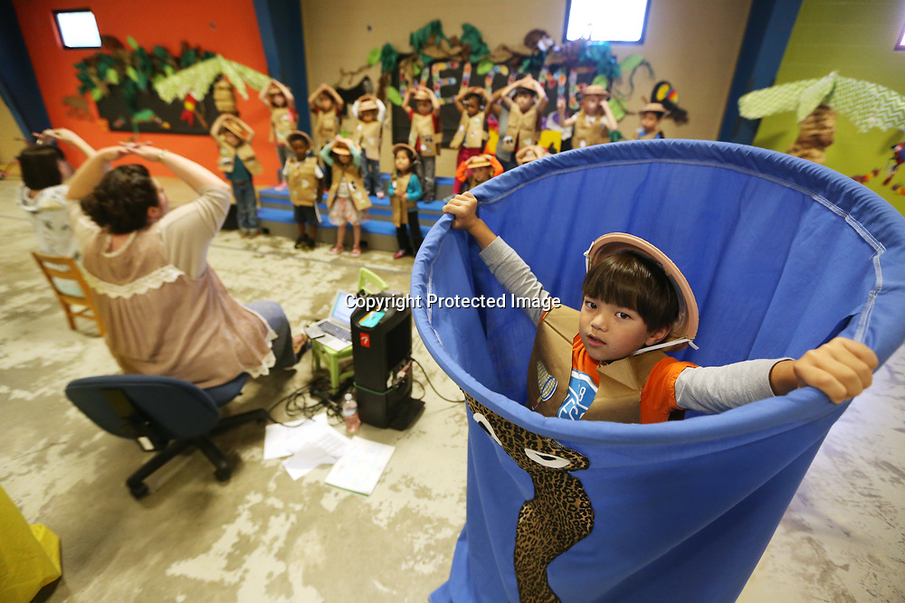 ECEC student Hiromasa Eason, right, acts like a snake as he and his classmates in Amanda Young's pre-k class rehearse their Jungle Beats performance with music teacher Aynsley Farmer, left, Monday morning at the school.