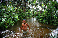 A Nukak-Maku Indian boy wades through a fresh water stream near his camp, just outside of San Jose de Guaviare on November 20, 2006. The Indians at the camp are now part of Colombia?s displaced community. With limited exposure to the western world they have left behind their nomadic traditions in the Colombian jungle in a large part due to fear of the FARC, the leftist rebels who control much of the jungle that was traditionally inhabited by the Indians and that is now being used by the FARC to produce cocaine which finances their war. (Photo/Scott Dalton)