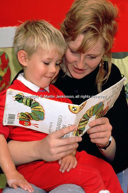 Helping a child learn to read at a preschool nursery....