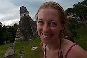 American tourist, Rachel Shockley, poses in front of the Temple of the Jaguar Priest, also known as Temple I, from atop of the Temple of the Mask, on the Great Plaza. The Temple of the Mask, also known as Temple II is one of the few temples that are still accessible to tourist in Tikal National Park in the Petén Basin in Northern Guatemala.