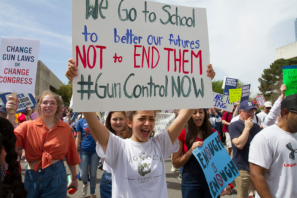 Students chant and hold up signs in protest for the lack of safety at schools across the country and the latest spate of shootings during the March for Our Lives event at Dallas City Hall.