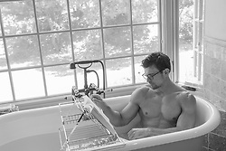 hot man in a bathtub reading a book