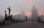 Sunrise at the Charles Bridge or Karluv most, built 1357 - 15th century, looking towards the Old Town bridge tower, with the Crucifix and Calvary sculpture, 1657, across the Vltava river in Prague, Czech Republic. Its construction began under King Charles IV, replacing the old Judith Bridge built 1158'??1172 after flood damage in 1342. This new bridge was originally called the Stone Bridge (Kamenny most) or the Prague Bridge (Prazsky most) but has been the Charles Bridge since 1870. The bridge is 621m long and nearly 10m wide, resting on 16 arches shielded by ice guards. It is protected by three bridge towers, two on the Lesser Quarter side and one in Gothic style on the Old Town side. The historic centre of Prague was declared a UNESCO World Heritage Site in 1992. Picture by Manuel Cohen