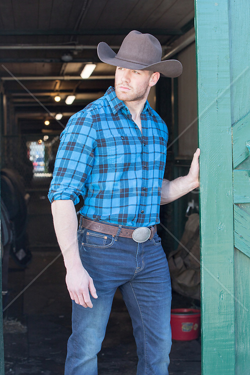 rugged cowboy standing in a doorway of a barn
