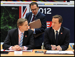 Britain's Prime Minister David Cameron with his Chief of Staff Ed Llewellyn (standing up) and his new Cabinet Secretary Jeremy Heywood (left) as the PM holds a cabinet meeting in the handball arena at the 2012 Olympic Games site London. As the London Olympics countdown enters its final 200 days Cameron highlighted the 'lasting legacy' the London 2012 Olympics will leave, with further venues securing long-term running contracts, Monday January 9, 2012. Photo By Andrew Parsons/ i-Images