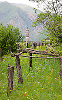 Ticino, Southern Switzerland. Moghegno. View of the bell tower through orchards with a tree-covered hillside looming in the background.