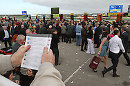 A man reading the race card in front of the bookies' stalls.
