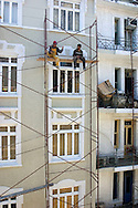 House painters take down scaffolding after finishing the facade of a building near Tünel in Istanbul, Turkey.