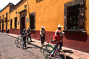 MEXICO, SAN MIGUEL ALLENDE Mexicans walking past colonial buildings