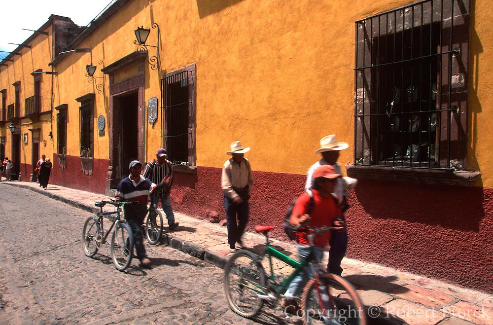 MEXICO, SAN MIGUEL ALLENDE Mexicans walking past colonial buildings