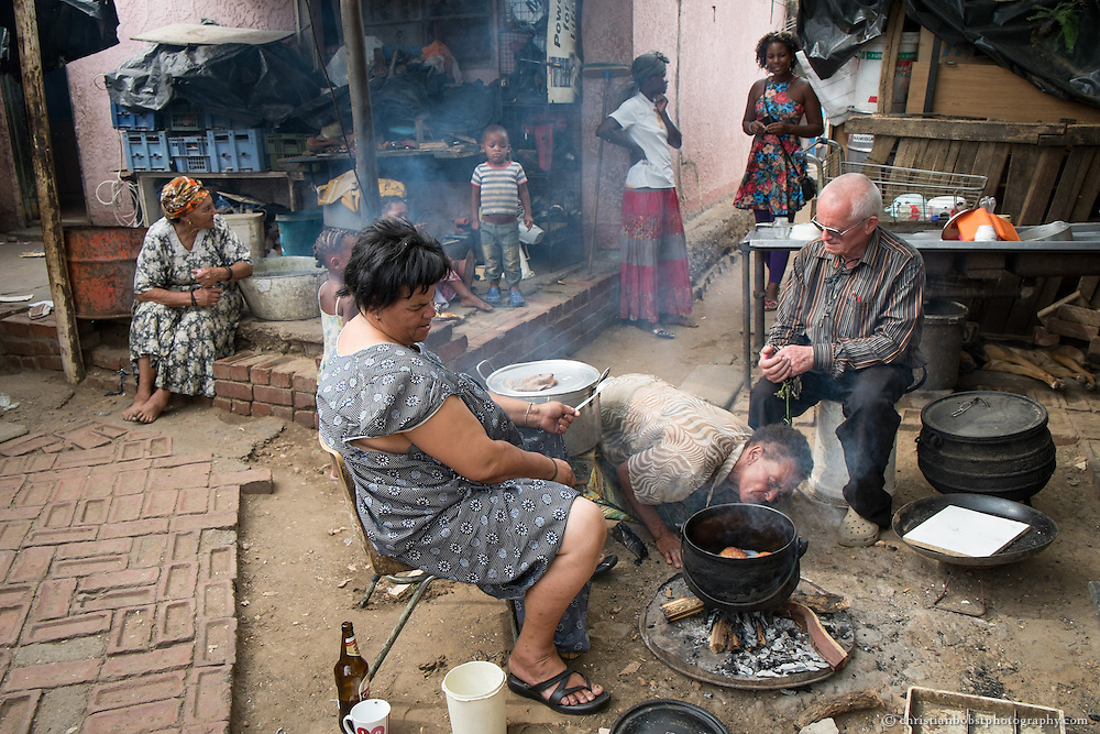 (2013) Father Hermann talks to some women who bake bread dough in hot oil to sell at a nearby school at Damara 6. Years ago they were also working as sex workers, but they say they are now too old to get enough clients to survive.
