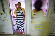 "24 MARCH 2004 - PHOENIX, AZ, USA: A Maricopa County Sheriff's Dept Detention Officer walks by juveniles sentenced as adults who are lined up in their cells during morning cell county in the Maricopa County Jail in Phoenix, AZ, March 24, 2004. The juveniles volunteer to serve Maricpoa County Sheriff Joe Arpaio's chain gang. The sheriff, who claims to be ""the toughest sheriff in America,"" has chain gangs in both the men's and women's jails and now has a chain gang for juveniles sentenced and serving time as adults in the county jail system. The sheriff claims it is the only juvenile chain gang in the country.   PHOTO BY JACK KURTZ"