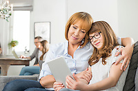 Affectionate mother and daughter using digital tablet with family sitting in background at home