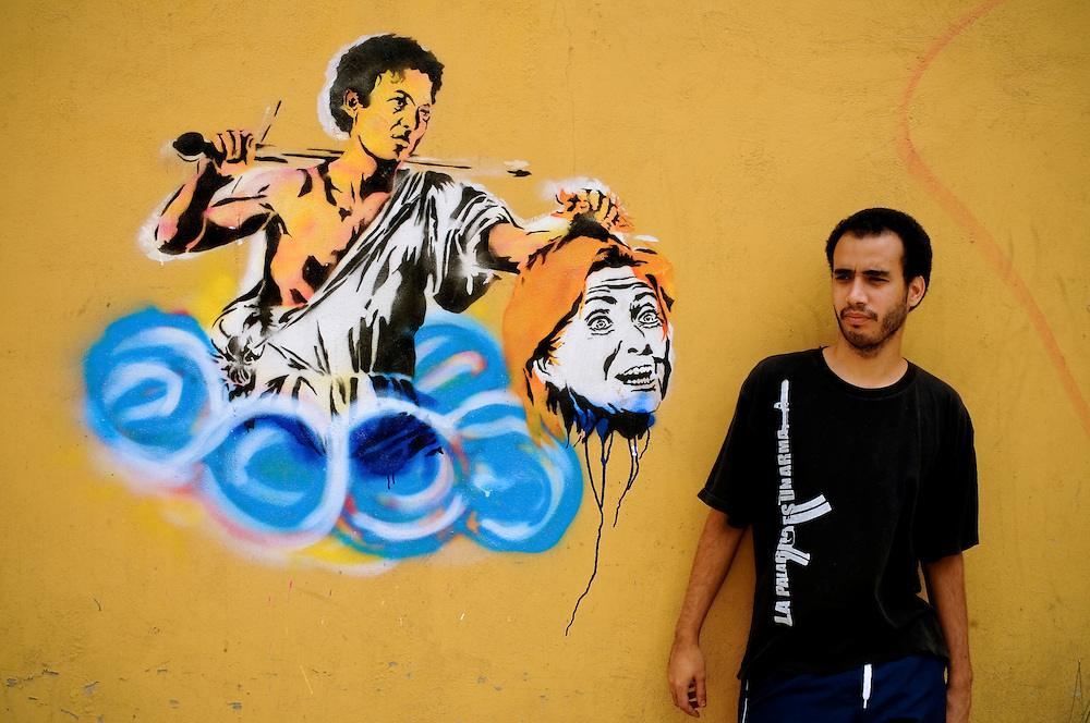 Carlos Zerpa, 26, a member of the Guerrilla Communications Collective, poses for a portrait of a stencil he painted in Caracas, Venezuela that depicts the Biblical David holding the decapitated head of Hillary Clinton (Goliath).  The Venezuelan government commissions collectives of graffiti artists like the Guerrilla Communications Collective to plaster the city in murals and stencils that promote the Bolivarian revolution and the political agenda of President Hugo Chavez.