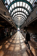 A Japanese male office worker or salaryman walks through an arched shopping arcade.near Iidabashi, Tokyo, Japan. Thursday, January 8th 2015