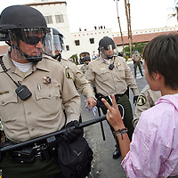 "A protestor makes a peace sign while approaching Riverside County Sheriff's deputies on the grounds of the Rancho Las Palmas Resort & Spa during an event dubbed the ""Koch Busters Rally"" on Sunday, January 30, 2011 in Rancho Mirage, Calif. Sunday's rally is a protest to an invitation-only gathering of elite Republican donors that is happening at the hotel. That four-day retreat, organized by billionaire brothers Charles and David Koch, is a strategy session to further a conservative political agenda. The Koch event started Saturday and runs through Tuesday. Crystal Chatham, The Desert Sun"